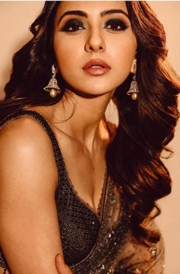 Hairstylist Tina Mukharjee left Rakul's hair in a bunch of brown wavy curls and makeup artist Chakravarthi Kadali added smokey eyes to complete the black vision