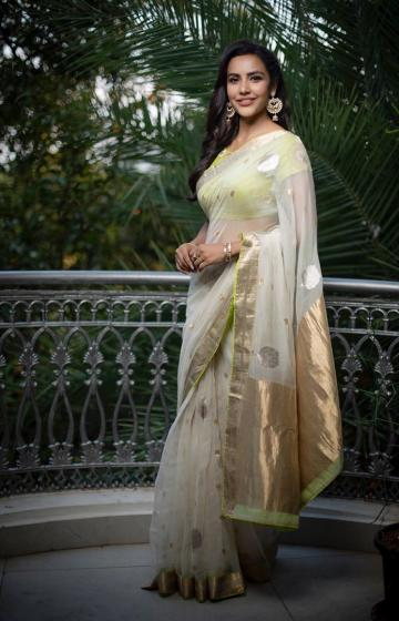 The white saree has gold zari, which is repeated in its green blouse along with floral designs - Fashion Models
