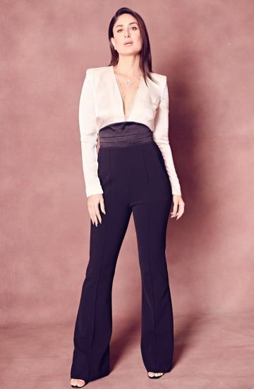 The white silk shirt has no buttons and is tucked into the high waisted bell bottom black pants - Fashion Models