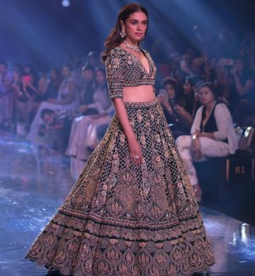 The lehenga from label Kalki has elbow-length sleeves and a pleated umbrella cut skirt - Fashion Models