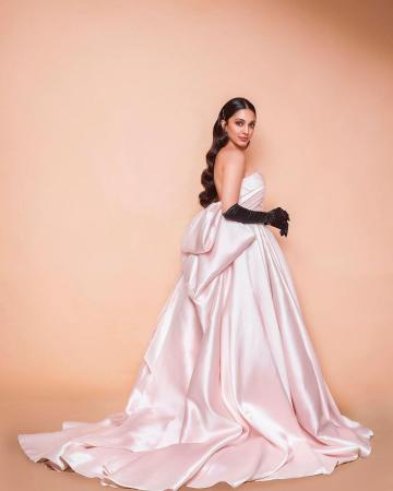 The pale satin off-shoulder gown has a voluminous skirt that blows out into an extended train with a huge bow in the back - Fashion Models