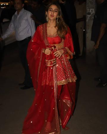 The bright red Anarkali with gold embroidery and embellishments has flared sleeves and the short skirt reminiscent of the Mughal age - Fashion Models