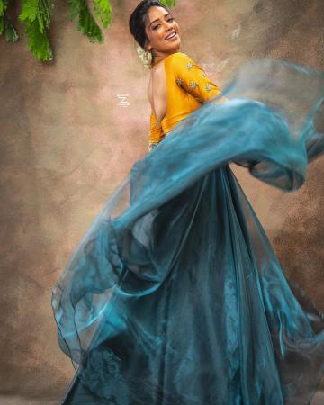 The mustard yellow blouse has a delightful peacock pair motif and the aqua blue skirt falls around her like flowing water - Fashion Models