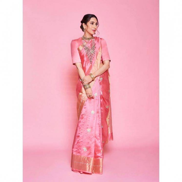 The pink saree with a gold zari border has simple flower motifs embroidered evenly on it - Fashion Models