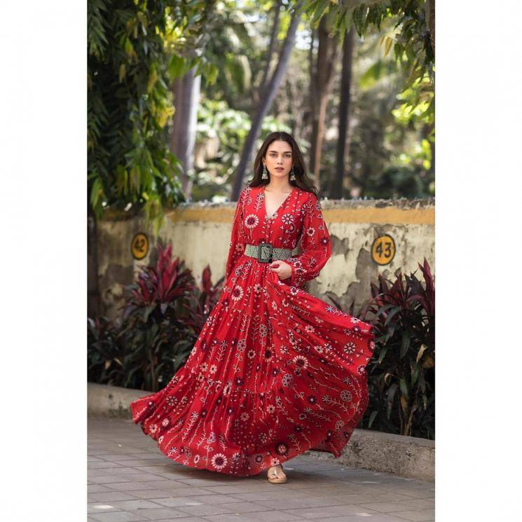 The deep-V neckline, simple floral prints, and the full, flowing skirt are the highlights of this outfit - Fashion Models