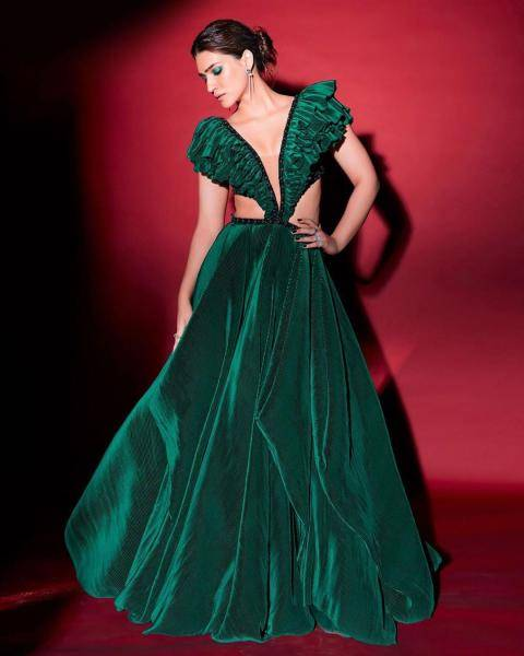 The ruffled top has a dramatic neckline and connects to a flared full skirt  - Fashion Models